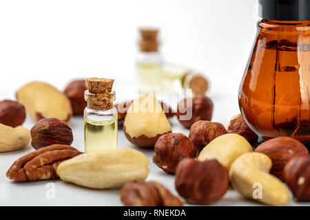 nut oil bottles and variety of nuts on white - Stock Photo