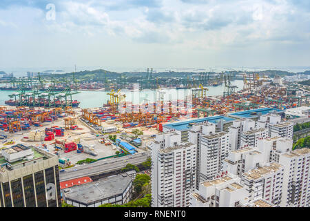 Aerial view of Singapore cargo shipping port with freight cranes and transportational containers, urban area with modern buildings in foreground - Stock Photo