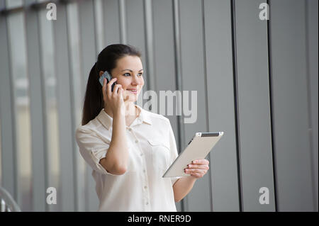 Young businesswoman talking on mobile phone by the window - Stock Photo