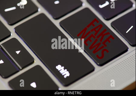 Fake news in internet laptop keyboard close up view - Stock Photo