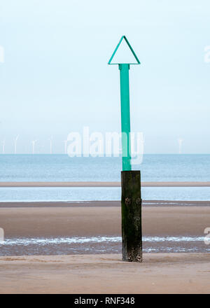 A green beach safety marker with a triangle on the top and an offshore windfarm in the distance off Rhyl beach, Denbighshire, North Wales - Stock Photo