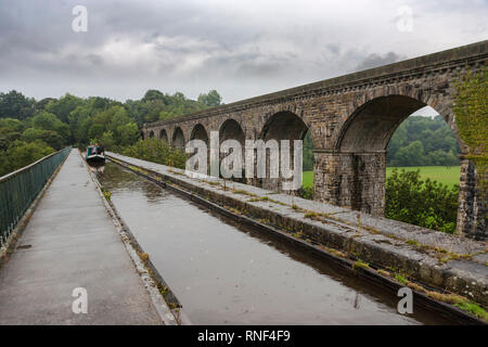 Narrowboat on the Chirk Aqueduct, Llangollen Canal, on the border between England and Wales in the pouring rain - Stock Photo