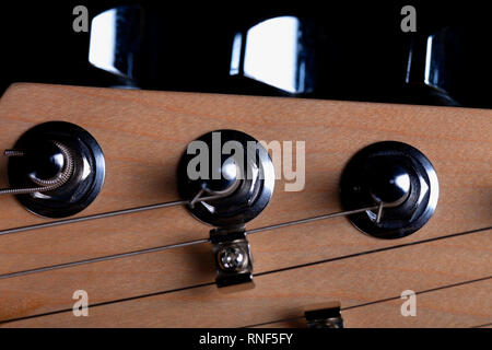 The headstock of an electric guitar on black background. - Stock Photo