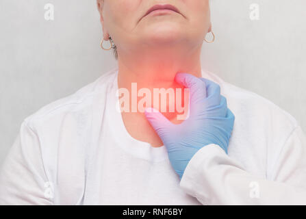 Doctor feels the thyroid gland in a patient of an adult woman, thyroid cancer, close-up, probing, carcinoma - Stock Photo