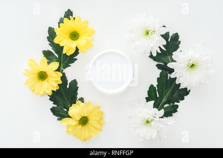 top view of compositions with chrysanthemums and beauty cream in bottle on white background - Stock Photo