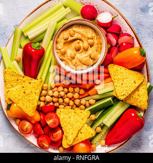 Hummus with various fresh raw vegetables, top view. - Stock Photo
