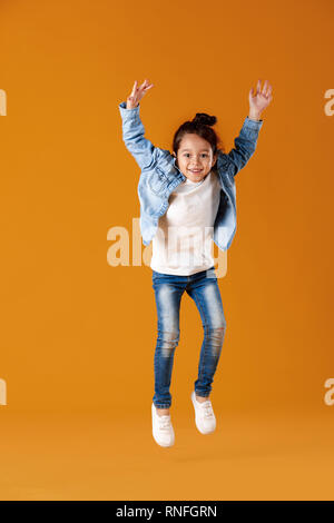 happy little child girl in jeans clothes jumping on orange background
