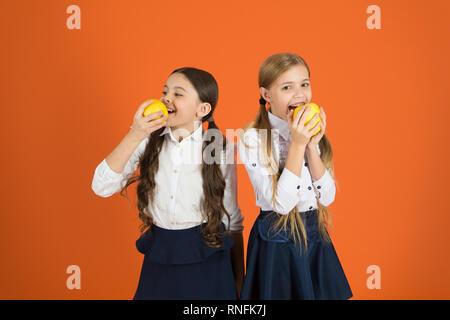 Schoolgirls eat apples. School lunch. Vitamin nutrition during school day. Boost student acceptance of fruit. Distributing free fresh fruit at school. Girls kids school uniform orange background. - Stock Photo