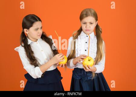 Boost student acceptance of fruit. Distributing free fresh fruit at school. Girls kids school uniform orange background. Schoolgirls eat apples. School lunch. Vitamin nutrition during school day. - Stock Photo