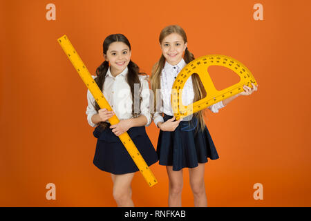 Geometry favorite subject. Education and school concept. School students learning geometry. Kids school uniform on orange background. STEM school disciplines. Pupil cute girls with big rulers. - Stock Photo