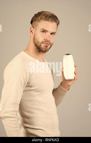 Man confident face holds shampoo bottle, grey background. Guy with bristle holds bottle shampoo, copy space. Hair care and beauty supplies concept. Man enjoy freshness after washing hair with shampoo. - Stock Photo