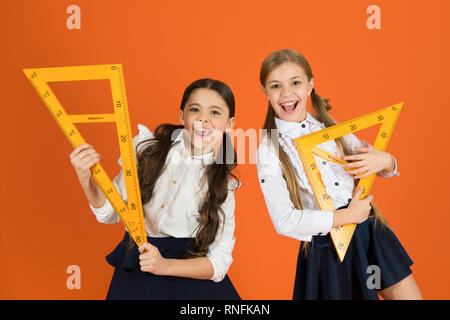 School students learning geometry. Kids school uniform on orange background. Pupil cute girls with big rulers. Geometry school subject. Drawing with ruler chalkboard. Education and school concept. - Stock Photo