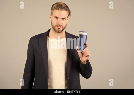 Man confident face holds shampoo bottle, grey background. Guy with bristle holds bottle shampoo, copy space. Man enjoy freshness after washing hair with shampoo. Hair care and beauty supplies concept. - Stock Photo