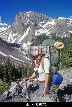 A female backpacker rests on a scree slope as she negotiates a rugged and alpine section of the Continental Divide Trail in the San Juan National fore - Stock Photo