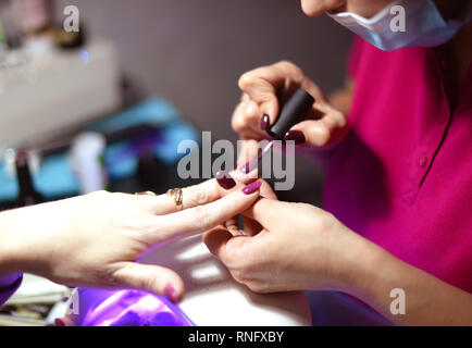 Coating gel varnish photography close-up.manicure in the salon. - Stock Photo