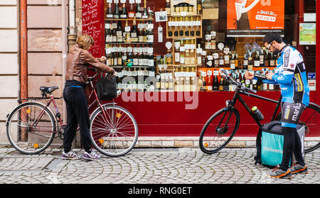 Strasbourg, France - Oct 1, 2017: Young Deliveroo biker wearing cycling branded outfit setting destination on smartphone The online food delivery company was founded in 2013 by Will Shu and Greg Orlowski - Stock Photo