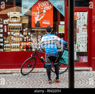 Strasbourg, France - Oct 1, 2017: Male Deliveroo biker wearing cycling branded outfit with big square heat rptective box. The online food delivery company was founded in 2013 by Will Shu and Greg Orlowski - Stock Photo