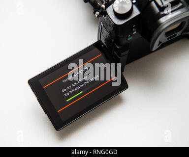 Paris, France Sep 30, 2017: Camera display showing firmware update process on the screen on modern Panasonic Lumix GH5 camera adding new functionalities  - Stock Photo