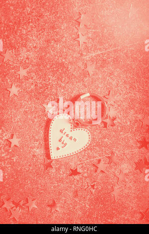Keyring in the shape of heart and slogan DREAM BIG. Minimalist Concept of ambitions and reaching goals, duotone image - Stock Photo