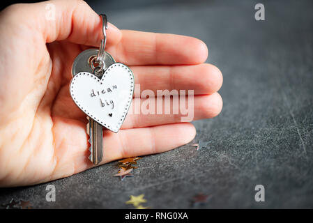 Keyring in the shape of heart and slogan DREAM BIG plus key from new home. Minimalist Concept of buying new home - Stock Photo