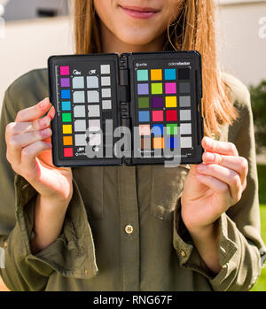 PARIS, FRANCE - SEP 30, 2018: Professional model holding Color Passport by X-Rite Color Reference Targets and camera calibration sfotware before the professional photo session shooting - Stock Photo