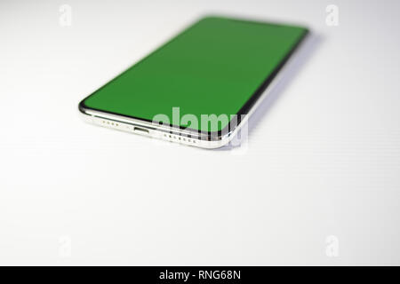 PARIS, FRANCE - SEP 27, 2018: Close-up shot of new Apple Computers iPhone Xs Max as hero object on white background - smartphone telephone with OLED display with green chroma key screen - large copy space - Stock Photo
