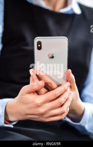 PARIS, FRANCE - OCT 2, 2018: business woman holding silver new Apple iPhone Xs Max smartphone telephone from Apple Computers with all home apps on OLED display - Stock Photo