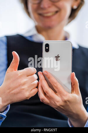 PARIS, FRANCE - OCT 2, 2018: business woman demonstration of the new Apple iPhone Xs Max smartphone telephone from Apple Computers with all home apps on OLED display - showing good ok sign - Stock Photo