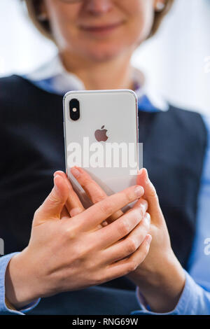PARIS, FRANCE - OCT 2, 2018: Happy business woman working on the new Apple iPhone Xs Max smartphone telephone from Apple Computers with all home apps on OLED display - Apple Computers Logo - Stock Photo