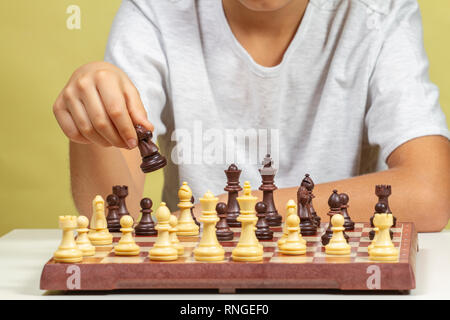 Kid sitting near chessboard and play chess game - Stock Photo