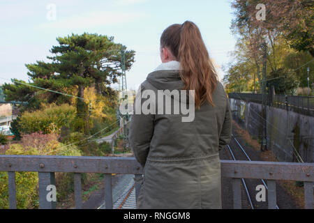 teenager girl is standing alone on a bridge and looks to the railroad tracks photographed from behind - Stock Photo