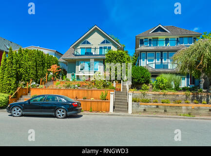 Suburban family houses with landscaped terraces and car parked in front - Stock Photo