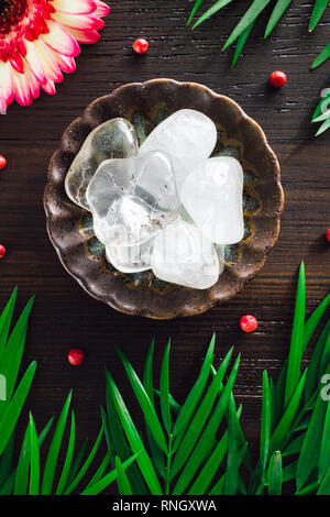 Polished Quartz Crystals with Mixed Flora on Dark Wood - Stock Photo
