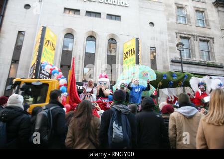 England, London, Westminster, Piccadilly, New Year's Day Parade, A float, with crowds surrounding and watching it pass by. - Stock Photo