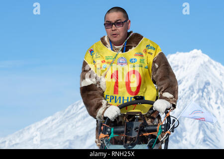 Portrait of running musher Nivani Ivan on background blue sky in winter sunny day. Kamchatka Sled Dog Race Beringia, Russian Cup of Dog Sled Racing - Stock Photo