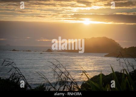 Golden sky and light as sun rises over Moturiki Island and Mount Maunganui Main Beach, Tauranga New Zealand