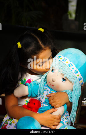 Indian small girl sitting and kissing her doll inside garden, Pune - Stock Photo