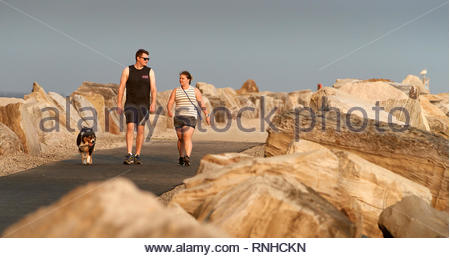 A young couple walking their dog along the break-wall beside the Clarence River, in-between large boulders, on a summer's evening in Yamba, Australia. - Stock Photo