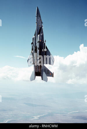 1980 - An air-to-air low angle left view of an F-15 Eagle aircraft in a vertical climb over the White Sands Missile Range at Holloman Air Force Base.  Two AIM-9 Sidewinder missiles are mounted on each wing and two AIM-7 Sparrow missiles are on each side of the fuselage - Stock Photo