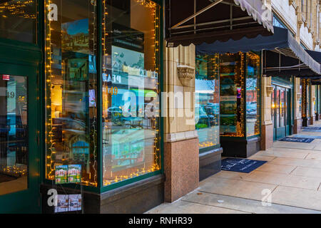 ASHEVILLE, NC, USA-2/16/19: Strings of lights and reflections fom the street shine in realtors' storefront windows along Page St. - Stock Photo