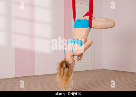 Fly yoga. The girl performs aerial yoga exercises. - Stock Photo