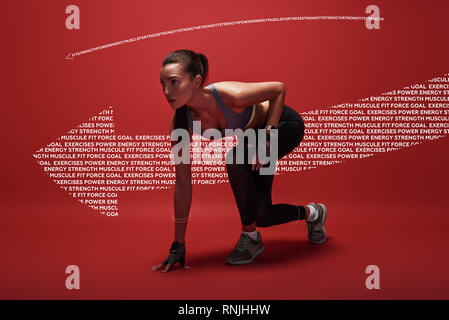 Attractive sportswoman in ready position to run. Girl on the knee, preparing to start jogging. Achievements and goals - Stock Photo