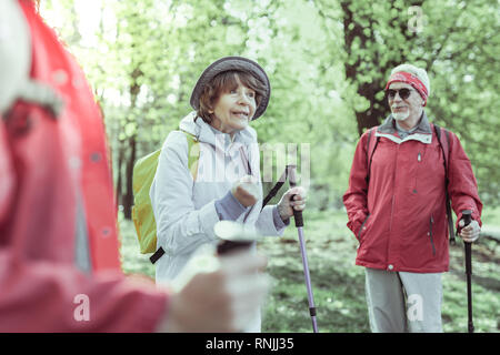 Elderly woman talking emotionally while hiking in the forest - Stock Photo