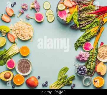Healthy smoothie ingredients on light table, top view, frame. Various fruits , vegetables and berries with almond, chia seeds and pine nuts for tasty  - Stock Photo