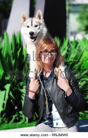 A close-up portrait of young caucasian blond haired girl and grey Siberian husky male dog on her shoulders. A woman wears black glasses, black jacket. - Stock Photo