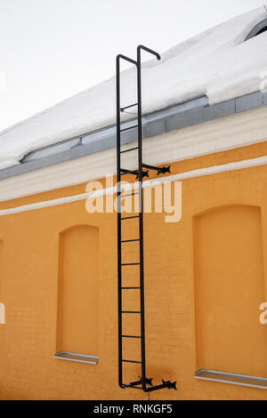 black metal ladder on yellow wall - Stock Photo