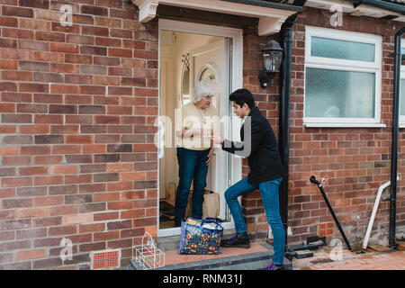 Teenage boy is delivering groceries to his grandmother. - Stock Photo