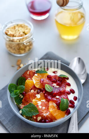 Bowl of homemade granola with yogurt, citrus and pomegranate seeds on gray wooden background. Selective focus. Healthy eating or vegetarian food conce - Stock Photo