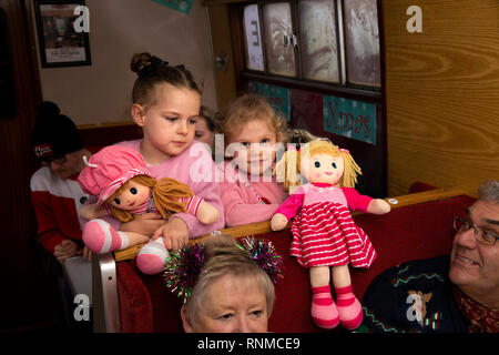 UK, England, Lancashire, East Lancashire Railway, Santa Special train, children with dolls watching magician - Stock Photo