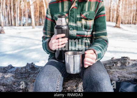 Pouring hot drink out of thermos at a campsite. Person in a winter forest during a hiking trip getting warm - Stock Photo
